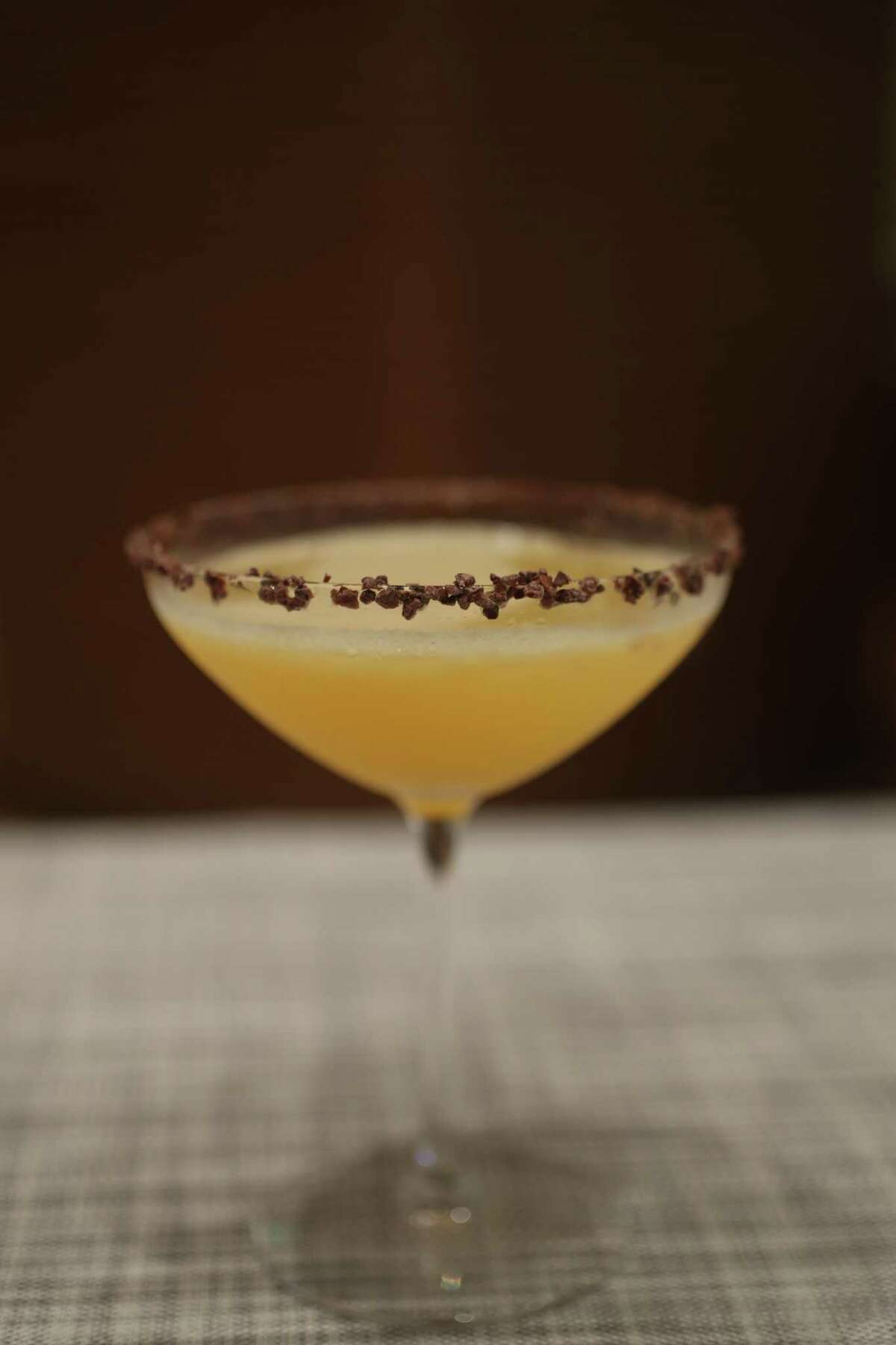 Late Checkout, a cocktail made with mezcal, wood-aged gin, orange liqueur, and passion fruit juice in a martini glass rimmed with Oaxacan chocolate at Xochi at Marriot Marquis Houston.