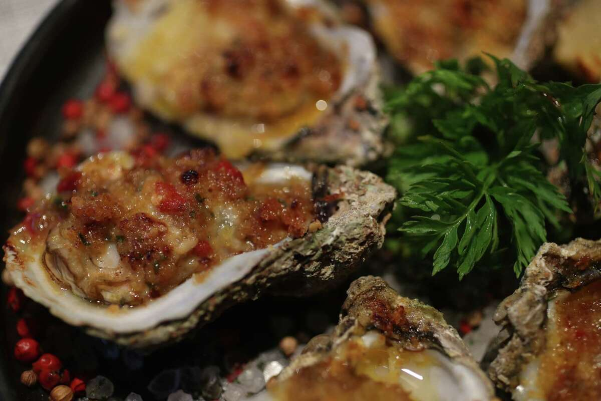 Ostiones de Lujo: wood-roasted oysters with mole amarillo butter at Xochi at Marriot Marquis Houston.