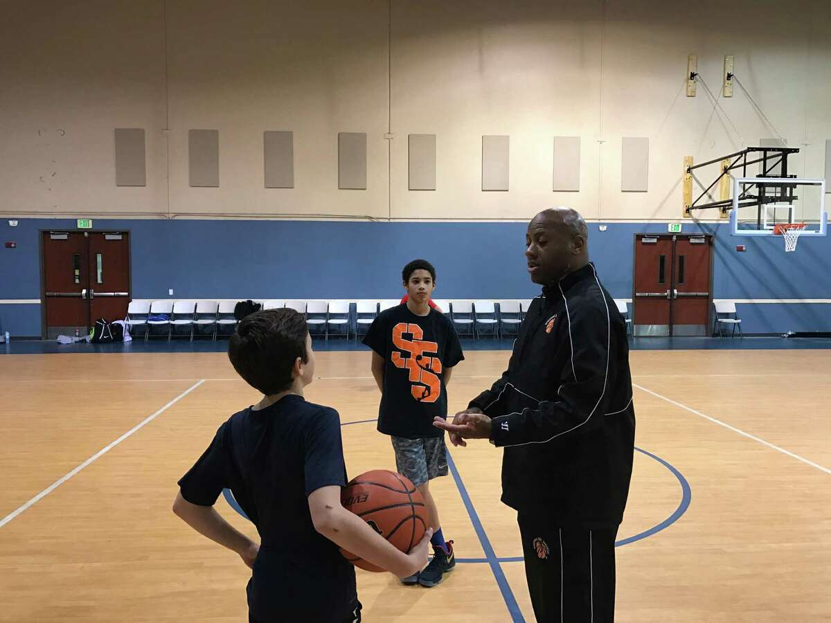 """Former professional basketball player David """"DJ"""" Jones leads practice on a recent night. Jones, who played 10 years in Europe, operates the """"Shooting for Success"""" program on the North Side."""