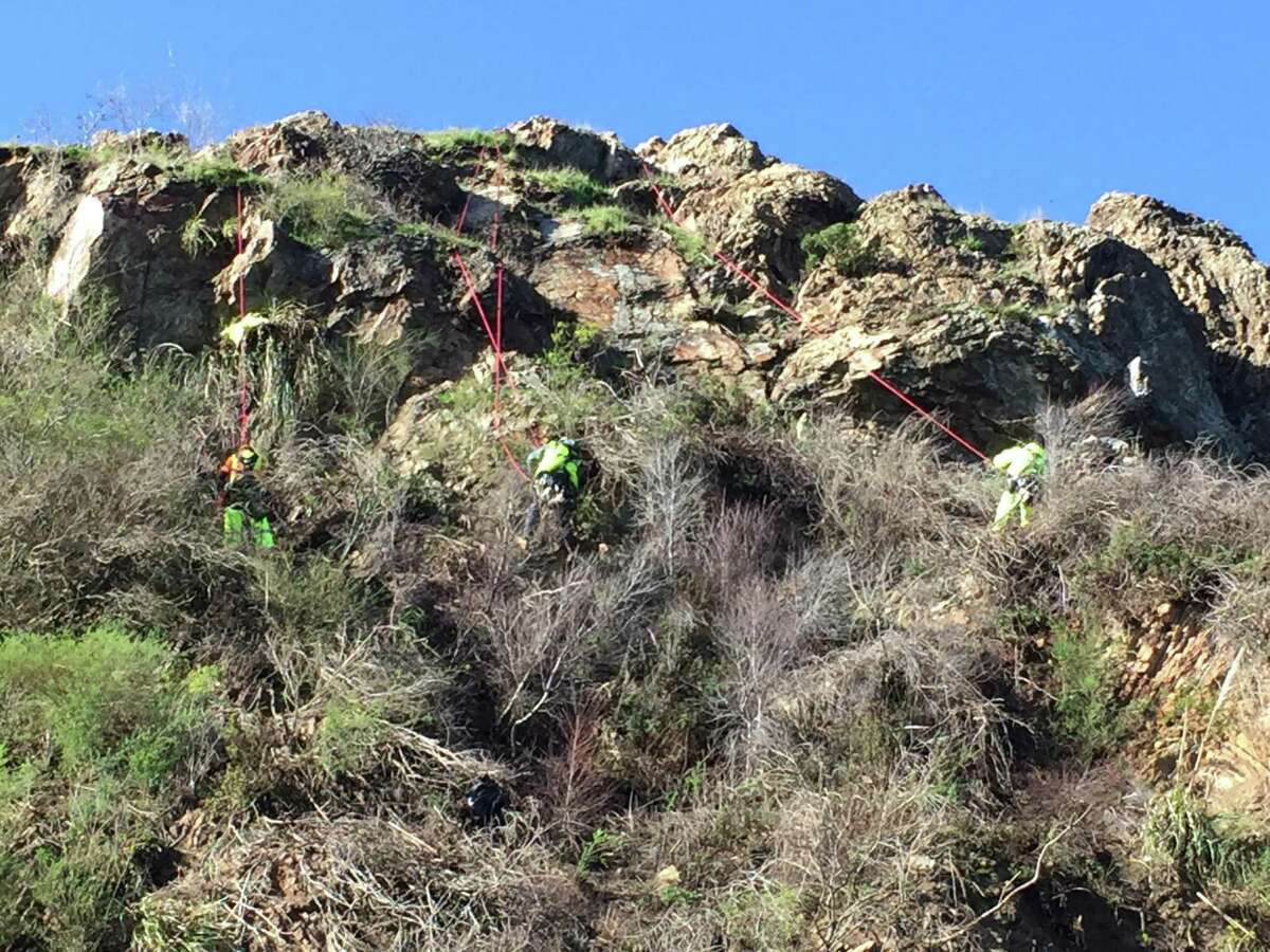 Repair workers dangled from ropes on the cliffside on O'Shaughnessy Boulevard between Del Vale Avenue and Malta Drive as they cleared the cliff of loose rocks.