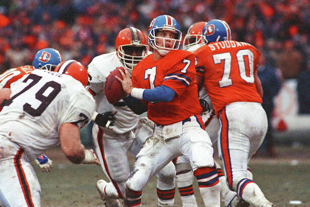 FILE - In this Jan. 12, 1987, file photo, Denver Broncos quarterback John Elway prepares to send the ball down field en route to a 23-20 overtime victory in the AFC Championship game against the Cleveland Browns, in Cleveland. On the sports misery index, Atlanta and Cleveland are hard to beat, and have come up with plenty of excruciating ways to come up short. (AP Photo/File)