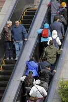 Riders take the escalator as they exit the Power St. BART station some standing to the right while others walk past on the left in San Francisco , Ca., on Thursday Jan. 19, 2017.