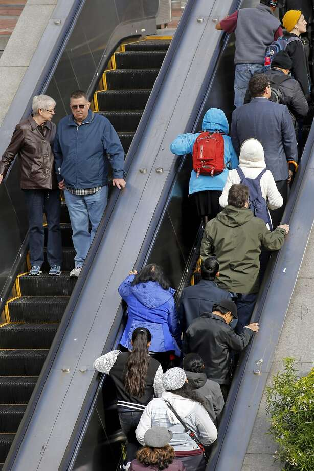 Riders take the escalator as they exit the Powell Street BART Station some standing to the right while others walk past on the left. Photo: Michael Macor, The Chronicle