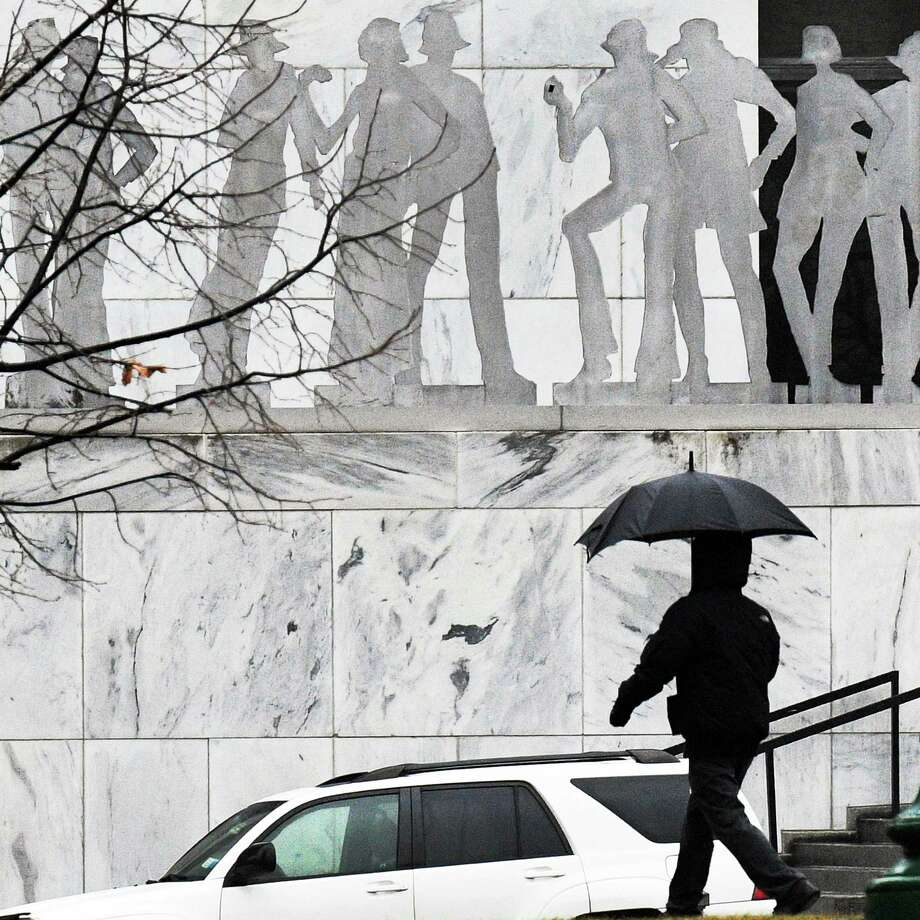An umbrella covered pedestrian walks past stauary outside the Legislative Office Building Wednesday Jan. 18, 2017 in Albany, NY.  (John Carl D'Annibale / Times Union) Photo: John Carl D'Annibale, Albany Times Union
