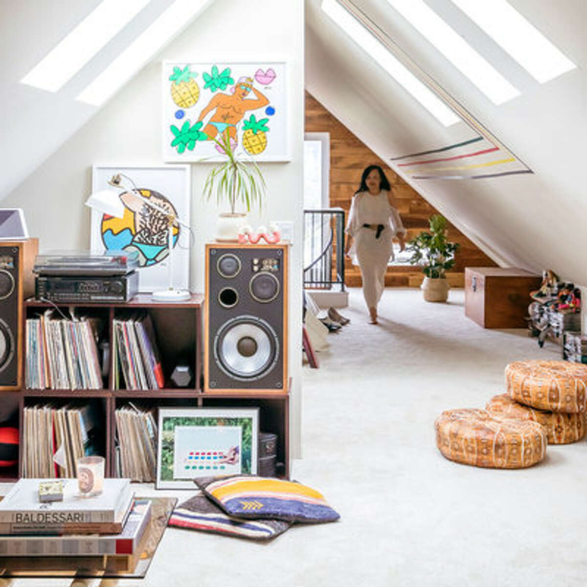 Sneak in storage The couple utilized a half wall in their attic bedroom to make space for their music collection. Records, speakers, and a turntable all fit tidily on modular stacking wood boxes.