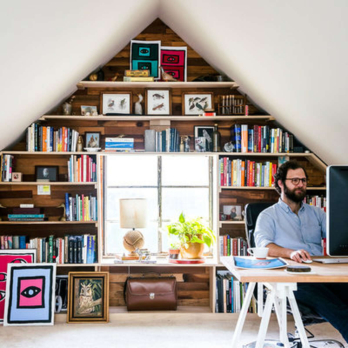 Work the walls The triangular shape of an attic wall can be the perfect backdrop for a high-impact bookshelf. Here, the couple paneled the back wall of their bedroom with redwood typically used for fencing, and then hung simple wood shelves for displaying books and curios.