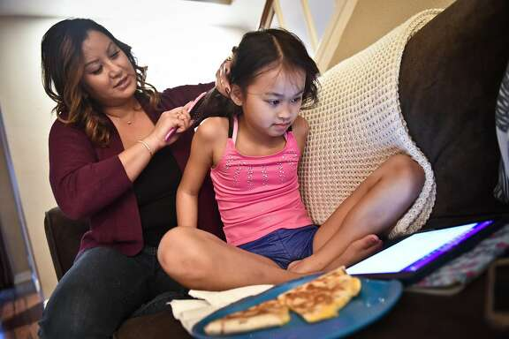 Tallia Hart, left, and her daughter Lola Bodenhamer, 9, right, at home after school Wednesday. Tallia was doing Lola's hair before gymnastics practice.  Newly elected San Francisco Chamber of Commerce President Tallia Hart and her daughter Lola Bodenhamer, 9, at their home and gymnastics practice on Wednesday, Jan. 18, 2017 in Trabuco Canyon, Calif.