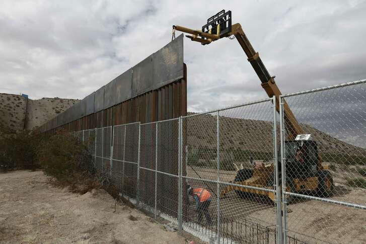 FILE - In this Nov. 10, 2016 file photo, workers raise a taller fence along the Mexico-US border between the towns of Anapra, Mexico and Sunland Park, New Mexico, where for almost two decades a Mass has been celebrated on Day of the Dead to remember migrants who have died trying to cross the fence. President-elect Donald Trump has threatened to force Mexico to pay for a wall along the nearly 2,000-mile (3,145-kilometer) border. (AP Photo/Christian Torres, File)