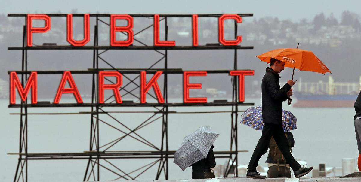 Pedestrians huddle under umbrellas as they walk past the Pike Place Market and in view of Elliot Bay behind, Wednesday, Jan. 18, 2017, in Seattle. Freezing rain, ice and fallen trees forced the closure of highways and roads in Oregon and Washington on Wednesday. Interstate 90, the main highway connecting western and eastern Washington, remained closed over Snoqualmie Pass until at least Thursday morning because of hazardous winter conditions.