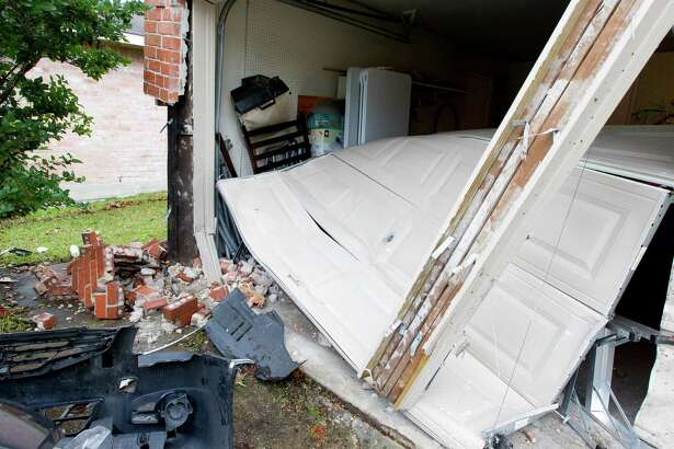 The garage of Eric Rivera's home is seen after Jose Mario Gazca drove his car into the side of Rivera's house damaging the lawn, several cars in addition to the garage around 1:45 a.m. Thursday, Jan. 19, 2017, in The Woodlands. Gazca has been charged with failure to stop and give information and false reporting to police. No injuries were reported.
