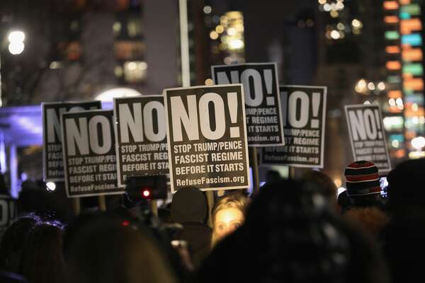 """People protest during a """"We Stand United"""" anti-Trump rally on January 19, 2017 in New York City. Thousands of people gathered outside the Trump International Hotel in Manhattan to protest on the eve of Donald Trump's inauguration as the 45th President of the United States."""