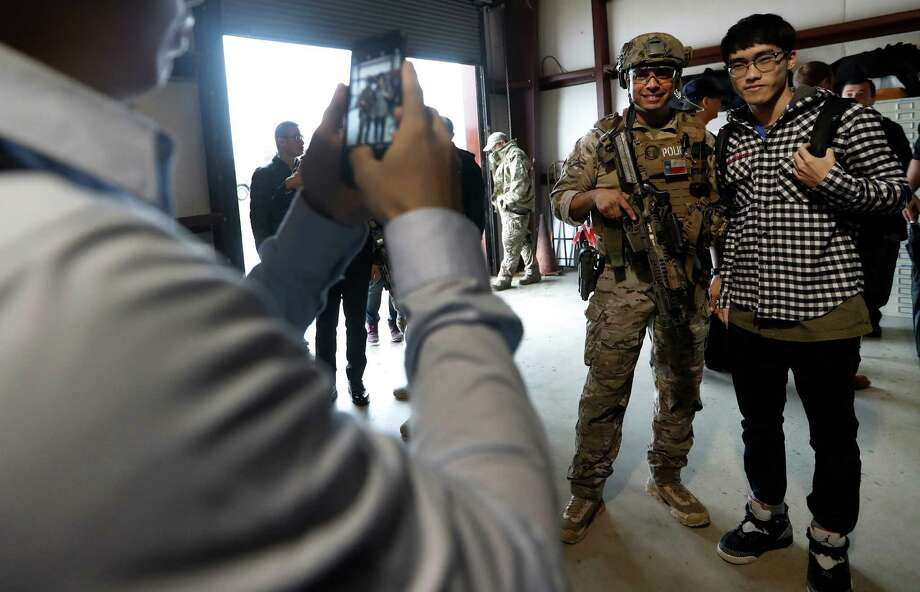 SWAT team member Joel Salazar takes photos with a member of the Central Police University in Taiwan during the students' tour of the Houston Police Academy on Thursday. Photo: Karen Warren, Staff Photographer / 2017 Houston Chronicle