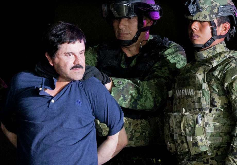 "FILE - In this Jan. 8, 2016 file photo, a handcuffed Joaquin ""El Chapo"" Guzman is made to face the press as he is escorted to a helicopter by Mexican soldiers and marines at a federal hangar in Mexico City. Guzman was convicted Tuesday of running an industrial-scale smuggling operation. Photo: Eduardo Verdugo / Copyright 2016 The Associated Press. All rights reserved."