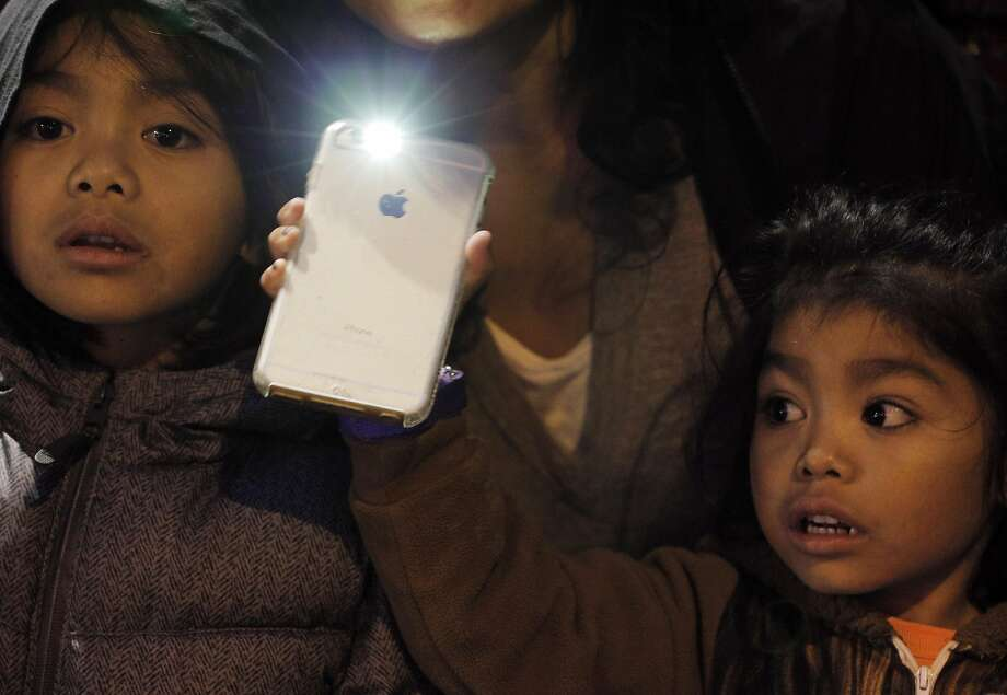 Mayari Duca, 4, and her brother, Joaquin Duca, 7, hold a light out side the Geary Theater on the night before Presi dent Trump's inauguration as part of the Ghost light Project. Theater ghost lights began as a superstition but are now used for safety. Photo: Carlos Avila Gonzalez, The Chronicle