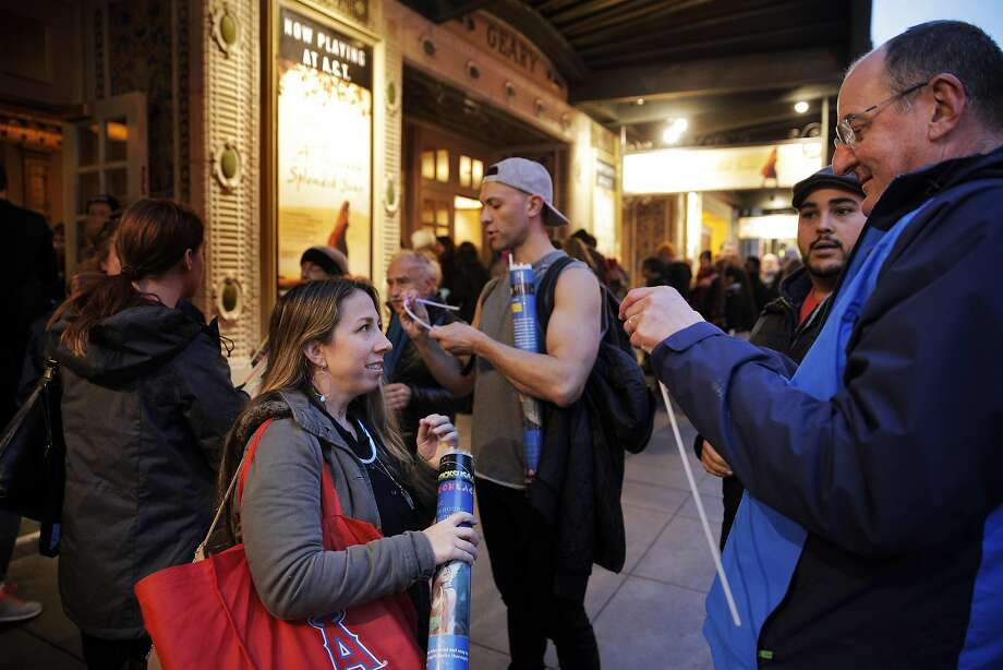 """Kate Jones, marketing director at New Conservatory Theater, center, distributes glow necklaces to those gathered at the Geary Theater in San Francisco, Calif., on Thursday, January 19, 2017. All across the country the night before the inauguration, theater artists are gathered to """"create light"""" in dark times ahead, standing in solidarity around the values of inclusion and compassion. The event gets its name from the theater tradition of a ghost light, where theaters leave a light on in an otherwise completely dark theater, originally for superstitious reasons; now the term applies as a safety measure. Photo: Carlos Avila Gonzalez, The Chronicle"""