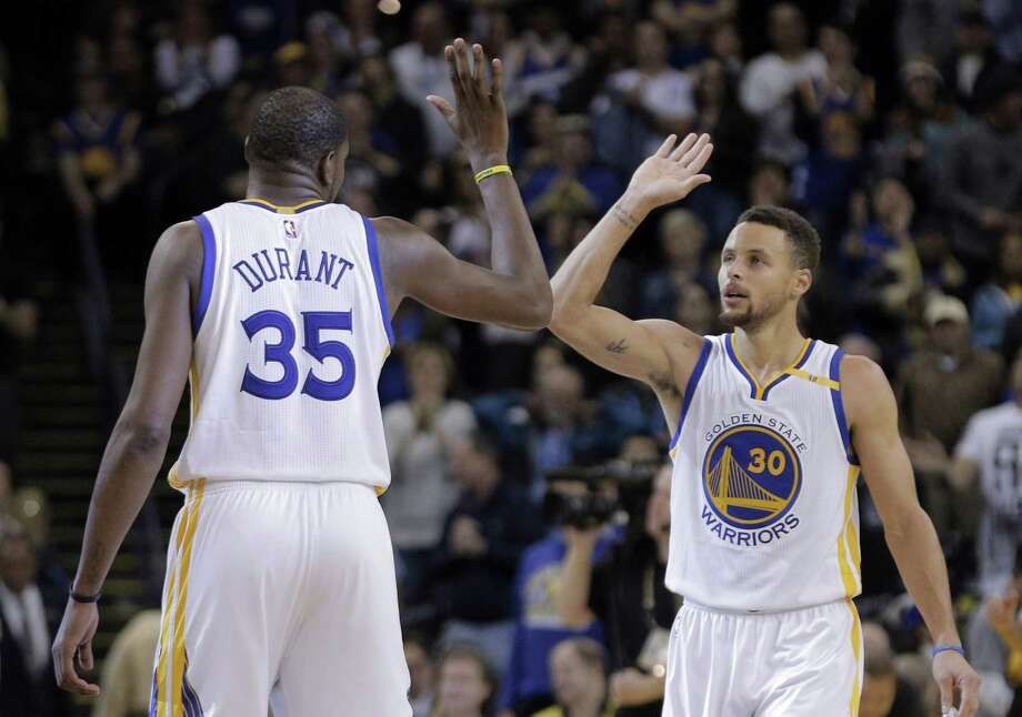 Kevin Durant (35) and Stephen Curry (30) high five in the second half as the Golden State Warriors played the Denver Nuggets at Oracle Arena in Oakland, Calif., on Monday, January 2, 2017. Photo: Carlos Avila Gonzalez / The Chronicle / Carlos Avila Gonzalez - San Francisco Chronicle