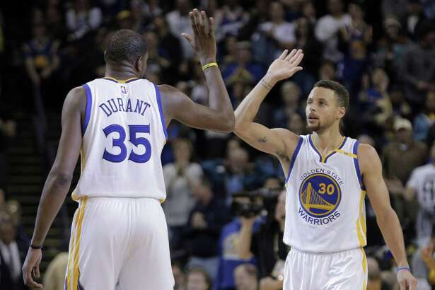 Kevin Durant (35) and Stephen Curry (30) high five in the second half as the Golden State Warriors played the Denver Nuggets at Oracle Arena in Oakland, Calif., on Monday, January 2, 2017.