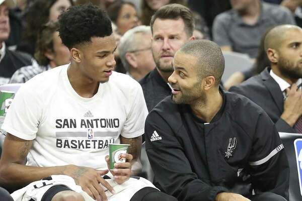 Tony Parker chats with Dejounte Murray on the bench as the Spurs host Denver at the AT&T Center on January, 19, 2017.
