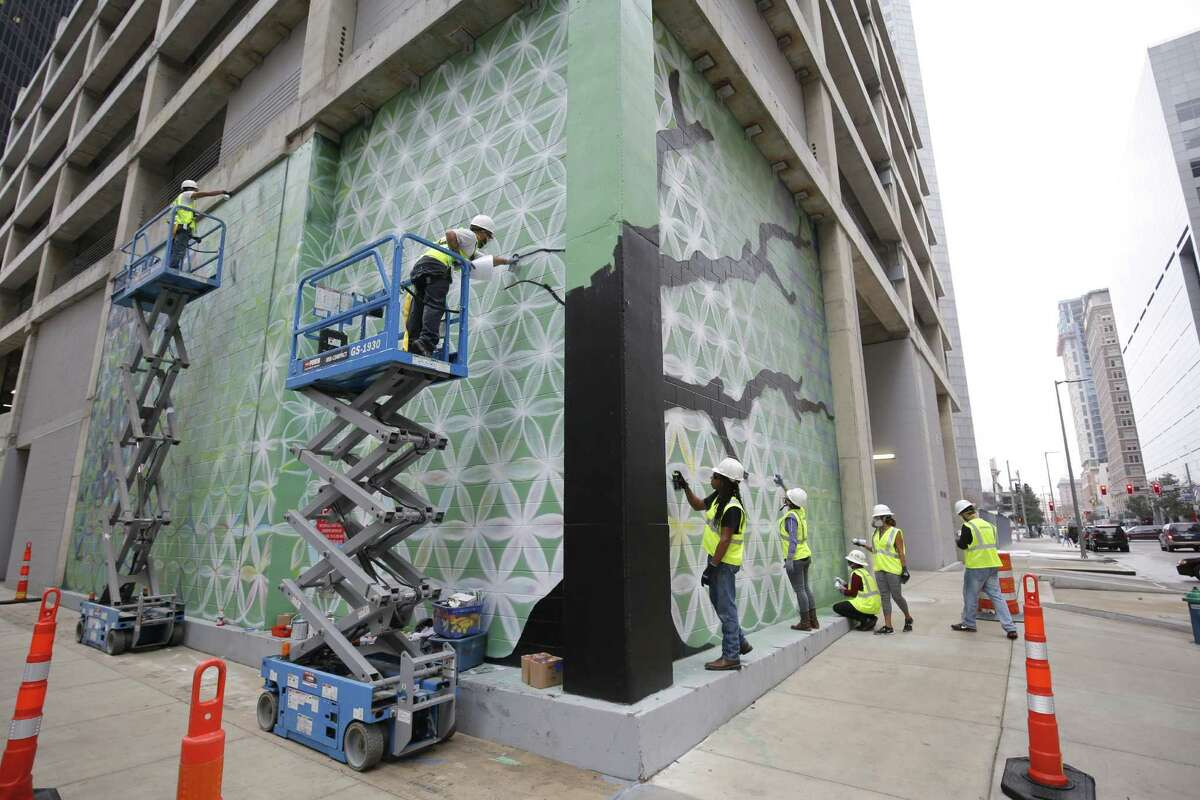 """Public artist Reginald Adams and his crew work on the Â?""""Tree of LifeÂ?"""" mural at the corner of Rusk and Travis, the site of SkanskaÂ?'s Capitol Tower development in downtown Houston. Photos provided by Skanska."""