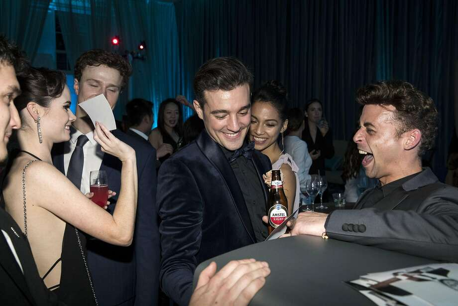 San Francisco Ballet company members Elizabeth Powell, Ben Freemantle, Diego Cruz, Isabella Devivo, and Taras Domitro (left to right) look over prints after taking a picture together at a photo booth during the after party for the San Francisco Ballet 2017 Opening Night Gala at City Hall in San Francisco, Calif., on Thursday, January 19, 2017. The theme of the evening was Ever Magical. Photo: Laura Morton, Special To The Chronicle