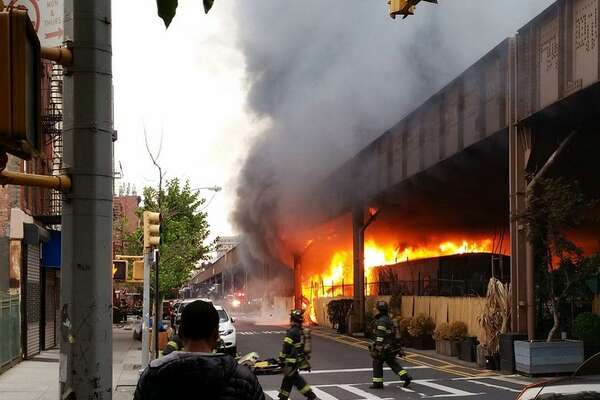 In this photo provided by Benjamin Parkin, firefighters battle a blaze at the Metro-North railroad tracks in New York, Tuesday, May 17, 2016. Train service into and out of Grand Central is being delayed due to the fire.