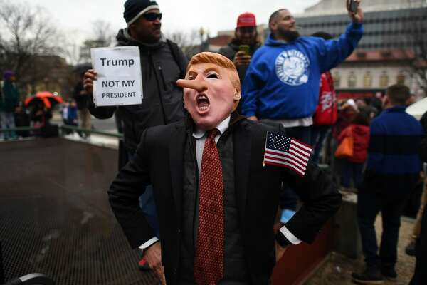 Demonstrators protest against US President-elect Donald Trump before his inauguration on January 20, 2017, in Washington, DC.         Donald Trump will be sworn in as the 45th president of the United States Friday -- capping his improbable journey to the White House and beginning a four-year term that promises to shake up Washington and the world.