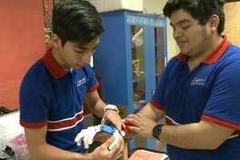 John Morales y David Navarro examinan los detalles de la impresión 3D de una mano prostética