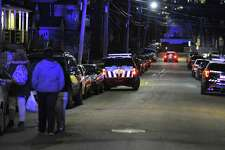 Residents return to their homes on Stamford's West side High Street following a police investigation on Thursday. Reports of shots fired in the area may be connected to a bodega shooting at West Main Convenience on West Main Street. The store is a few blocks from High Street.