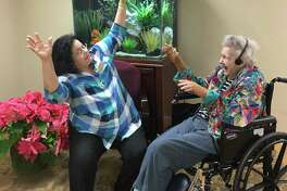 Nancy Lyles, Treemont Health Care Center's activity director and coordinator of the Music and Memory program, engages with resident Isabelle, who clearly enjoys her gospel music, which has a positive impact on her demeanor.