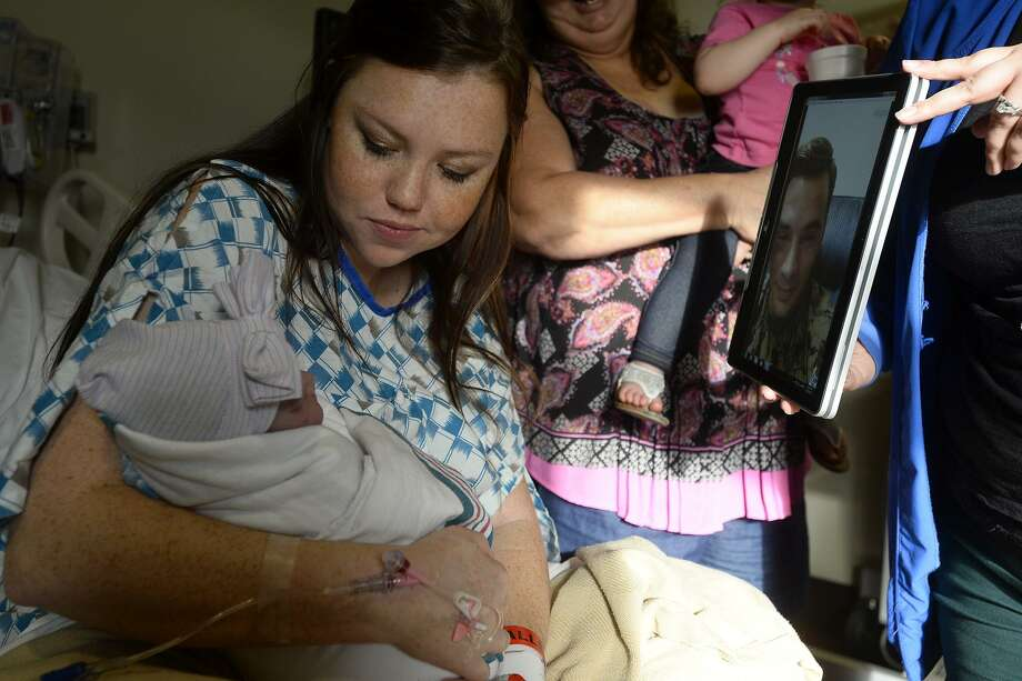 Kellie Soto holds her newborn daughter, Mila, while husband Anthony watches via Skype at Baptist Hospital on Thursday afternoon. Anthony is deployed in Okinawa, Japan with the Marines but was able to watch Mila's birth via a Skype video chat. Due to time zone differences, Anthony had been up for more than 27 hours.  Photo taken Thursday 1/19/17 Ryan Pelham/The Enterprise Photo: Ryan Pelham / Ryan Pelham/The Enterprise / ©2017 The Beaumont Enterprise/Ryan Pelham