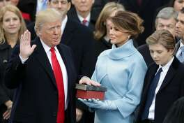 U.S. President Donald Trump takes the oath of office as his wife Melania Trump holds the bible and his son Barron Trump looks on, on the West Front of the U.S. Capitol on January 20, 2017 in Washington, DC. In today's inauguration ceremony Donald J. Trump becomes the 45th president of the United States.  (Photo by Chip Somodevilla/Getty Images)