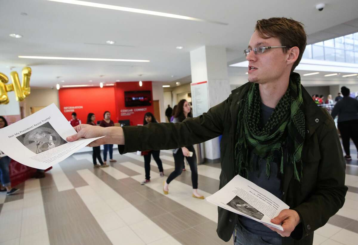 Students for A Democratic Society Coordinator Fabian Sneevliet passes out flyers for a protest against President Donald J. Trump during the inauguration ceremony at the school's watch party at student center on Friday, January 20, in Houston.