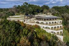 "Driving north on U.S. 281, it's hard to miss the miniature coliseum-like mansion perched on a bluff overlooking the Olmos Dam since 1986. The 6,500-square-foot ""landmark residence""  is now on the market for $4,999,000. A luxe history and list of amenities tie the price tag to the home."