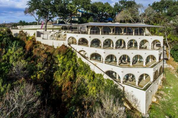 """Driving north on U.S. 281, it's hard to miss the miniature coliseum-like mansion perched on a bluff overlooking the Olmos Dam since 1986. The 6,500-square-foot """"landmark residence""""  is now on the market for $4,999,000. A luxe history and list of amenities tie the price tag to the home."""