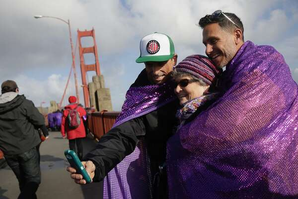 James Bosch (l to r), Pam Pitt and John Rowe take a selfie together as they stand on the Golden Gate Bridge for Bridge Together on Friday, January 20, 2017 in San Francisco, California.