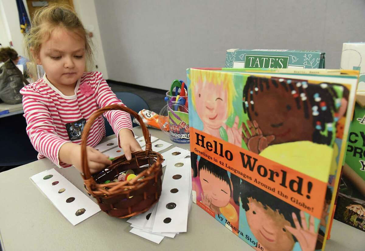 """Amelia Tice, 5, of Guilderland works on a exercise where she places the same size and color buttons on a strip of paper with pictures of buttons during the """"All Aboard to 1,000 Books Before Kindergarten!"""" event at Guilderland Public Library on Friday, Jan. 20, 2017 in Guilderland, N.Y. (Lori Van Buren / Times Union)"""