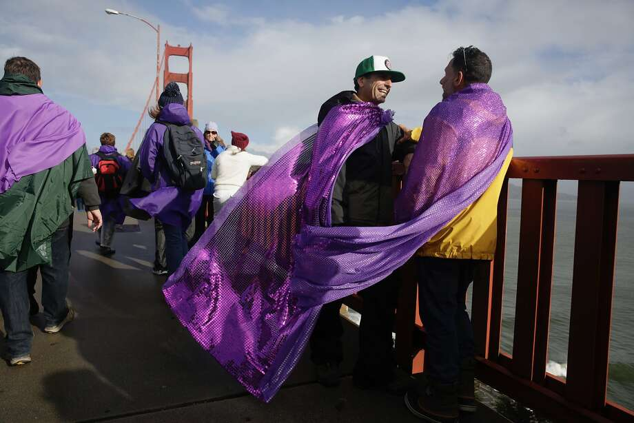 James Bosch (l to r) and John Rowe, both of San Francisco, wear purple capes as they stand on the Golden Gate Bridge with others before Bridge Together on Friday, January 20, 2017 in San Francisco, California. Photo: Lea Suzuki, The Chronicle