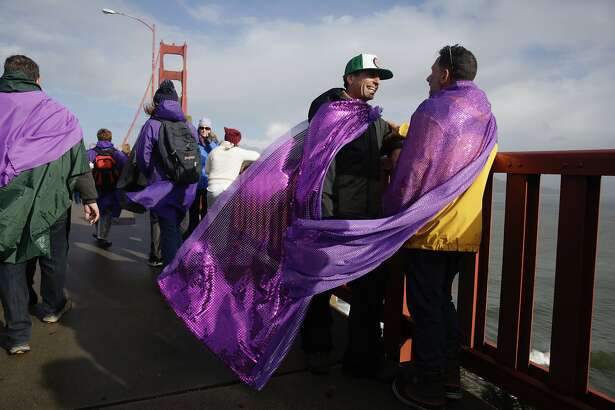 James Bosch (l to r) and John Rowe, both of San Francisco, wear purple capes as they stand on the Golden Gate Bridge with others before Bridge Together on Friday, January 20, 2017 in San Francisco, California.