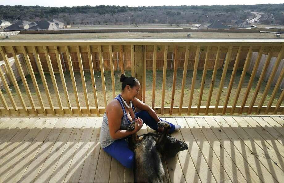Maritza Arroyo plays with her German shepherd on her balcony overlooking the Ladera master-planned community. Photo: Kin Man Hui /San Antonio Express-News / ©2017 San Antonio Express-News