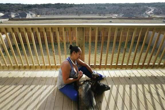 Maritza Arroyo plays with her German shepherd on her balcony overlooking the Ladera master-planned community.