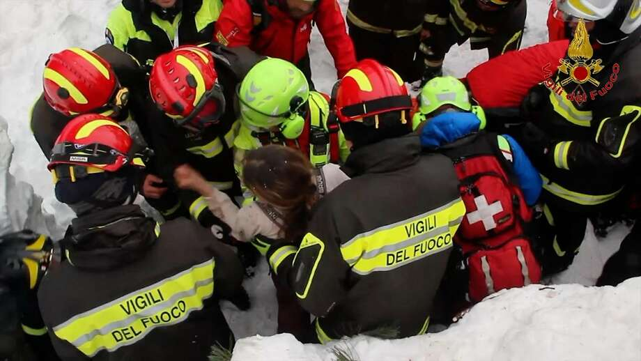 Firefighters rescue a woman from under snow and debris after an avalanche hit a hotel in Rigopiano, Italy. Photo: Italian Firefighters, Associated Press
