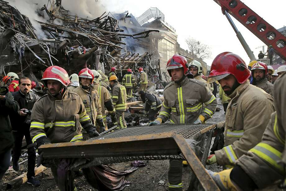Firefighters remove debris from a 17-story building in the heart of Tehran that collapsed and burned. Photo: Ebrahim Noroozi, Associated Press