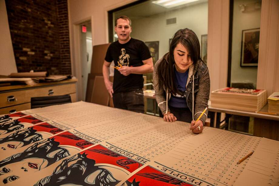 """San Antonio-based photographer Arlene Mejorado signs copies of """"We the People Defend Dignity,"""" the poster she collaborated on with Shepard Fairey. Photo: Courtesy Ayse Gursoz"""