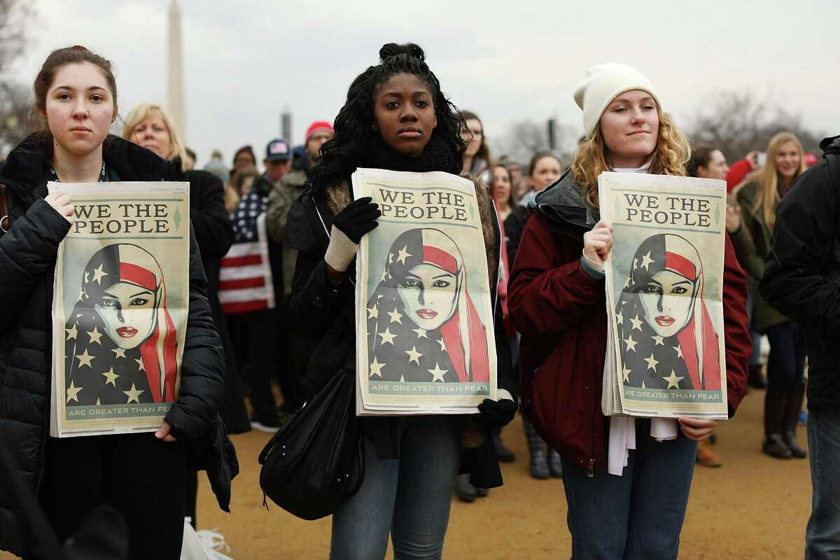 Three women hold a poster from the We the People campaign while watching the inauguration of President Trump from the National Mall on Friday.