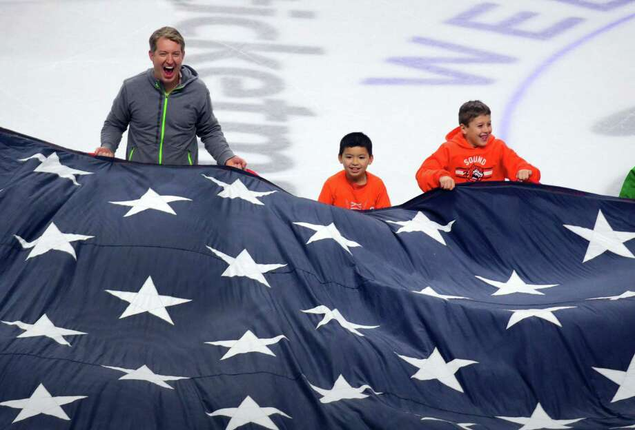 Fairfield's Brendan Mullahy, left, ruffles the American flag with Alex Lau, 9, and Alex DeLuca, 8, as part of the Military Appreciation Night ceremony held before the start of Sound Tigers hockey action against the Utica Comets at the Webster Bank Arena in Bridgeport Jan. 14. Photo: Christian Abraham / Hearst Connecticut Media / Connecticut Post
