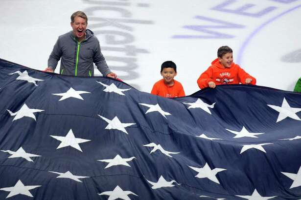 Fairfield's Brendan Mullahy, left, ruffles the American flag with Alex Lau, 9, and Alex DeLuca, 8, as part of the Military Appreciation Night ceremony held before the start of Sound Tigers hockey action against the Utica Comets at the Webster Bank Arena in Bridgeport Jan. 14.