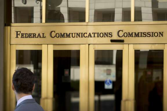 "A man looks at the Federal Communications Commission (FCC) headquarters in this photo taken with a tilt-shift lens in Washington, D.C., U.S., on Monday, Nov. 10, 2014. President Barack Obama called for the ""strongest possible rules"" to protect the open Internet, advocating stricter controls than a regulator he appointed and causing shares of Comcast Corp. and other broadband providers to drop. Obama's comments tilt the White House against positions advocated by broadband providers and FCC Chairman Tom Wheeler. Photographer: Andrew Harrer/Bloomberg"