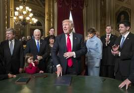 President Donald Trump is joined by the Congressional leadership and his family as he formally signs his cabinet nominations into law, Friday, Jan. 2017, in the President's Room of the Senate on Capitol Hill in Washington. Joining him from left are Sen. Roy Blunt, R-Mo., Vice President Mike Pence and his wife Karen Pence, Jared Kushner, President Trump's wife Melania Trump, Eric Trump, and Speaker of the House Paul Ryan, R-Wis. (AP Photo/J. Scott Applewhite, Pool)