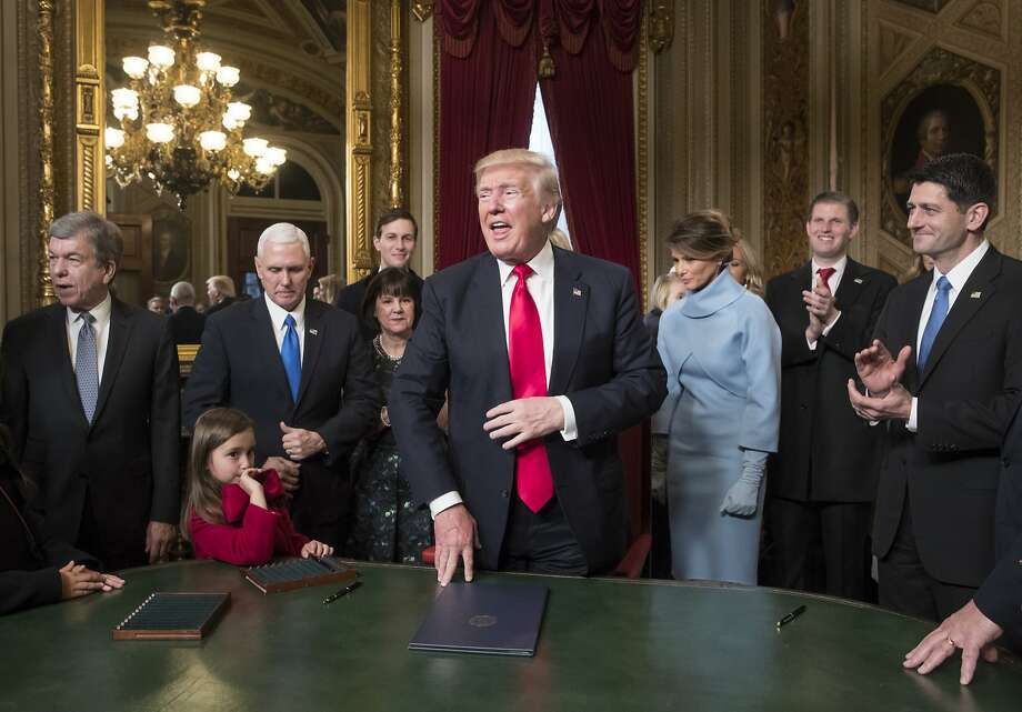 President Donald Trump is joined by the Congressional leadership and his family as he formally signs his cabinet nominations into law, Friday, Jan. 2017, in the President's Room of the Senate on Capitol Hill in Washington. Joining him from left are Sen. Roy Blunt, R-Mo., Vice President Mike Pence and his wife Karen Pence, Jared Kushner, President Trump's wife Melania Trump, Eric Trump, and Speaker of the House Paul Ryan, R-Wis. (AP Photo/J. Scott Applewhite, Pool) Photo: J. Scott Applewhite, Associated Press