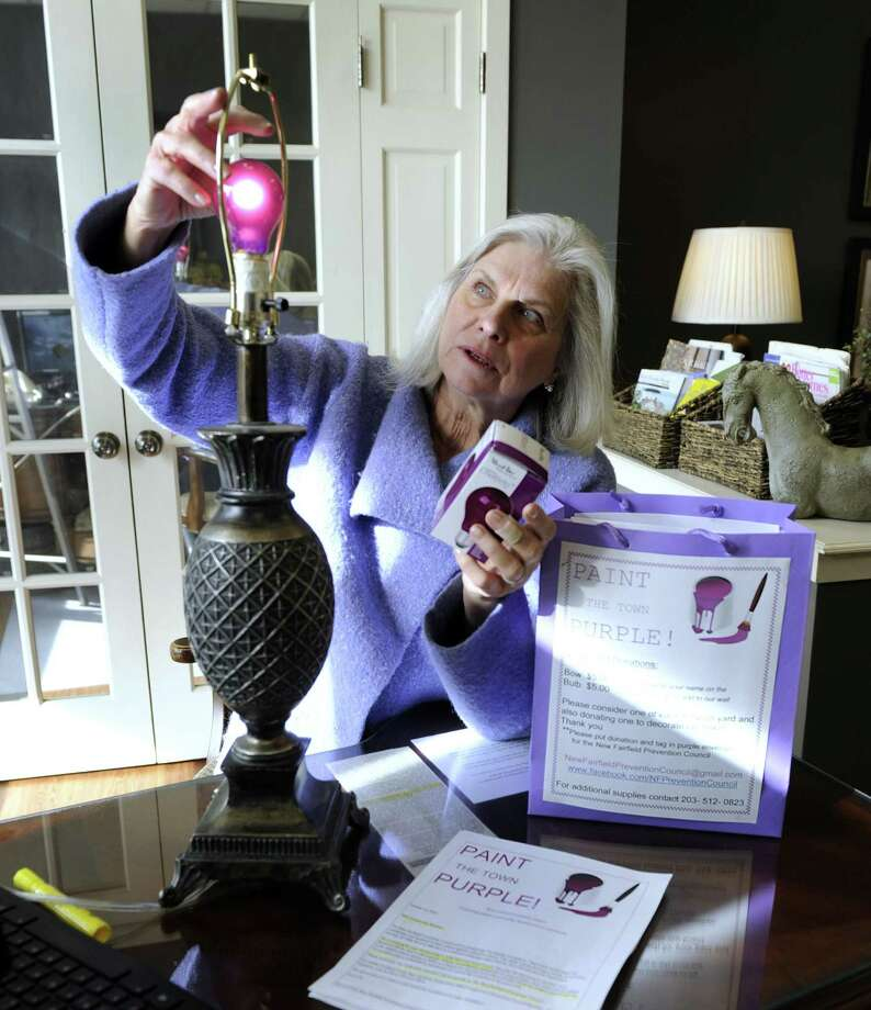 "Claire Luks, owner of Luks Realty, changes a lamp bulb to a purple one in her office Friday, January 22, 2016. Luks is helping to promote ""Go Project Purple,"" sponsored by the New Fairfield Prevention Council to encourage the community and students to take a stand against substance abuse. Photo: Carol Kaliff / Hearst Connecticut Media / The News-Times"